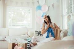 Le kvinnan med nya gåvor på baby showerpartiet arkivbild