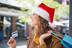 Le kvinnan med santa hatt- och shoppingpåsar Royaltyfri Fotografi