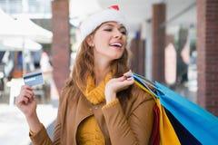 Le kvinnan med santa hatt- och shoppingpåsar Arkivbilder