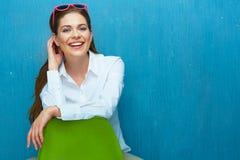 Le kvinnan med solglasögon som placerar på stol mot blått Royaltyfri Foto