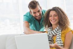 Le kvinnan på soffan som visar hennes Co-arbetare hennes bärbar dator Arkivfoto