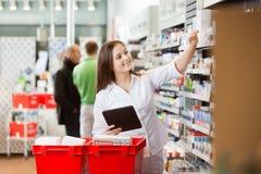Le kvinnan som använder den Digital minnestavlan för att shoppa på arkivfoton