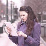 Le kvinnan som använder digitalt minnestavlaanseende på stadsgatan royaltyfria bilder