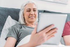Le kvinnan som använder minnestavlan, medan ligga i säng hemma Royaltyfri Foto