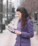 Le kvinnan som anv?nder digitalt minnestavlaanseende p? stadsgatan arkivfoton