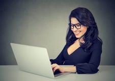 Le kvinnan som arbetar med bärbara datorn royaltyfria foton