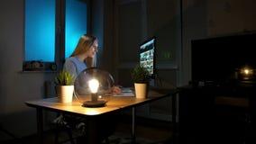 Le kvinnan som arbetar på datoren på natten Le kvinnlign i rutigt skjortasammanträde på tänt av träskrivbordet för liten lampa lager videofilmer