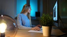 Le kvinnan som arbetar på datoren på natten Le kvinnlign i rutigt skjortasammanträde på tänt av träskrivbordet för liten lampa stock video