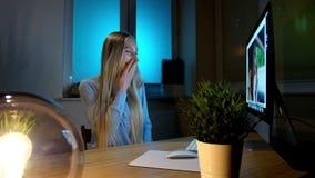 Le kvinnan som arbetar på datoren på natten Le kvinnlign i rutigt skjortasammanträde på tänt av träskrivbordet för liten lampa arkivfilmer