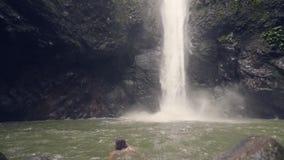 Le kvinnan som badar i bergsjön på den flödande vattenfallet för bakgrund i tycka om för kvinna för tropisk skog som lyckligt är  arkivfilmer