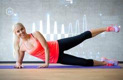 Le kvinnan som gör övningar på mattt i idrottshall Royaltyfri Bild
