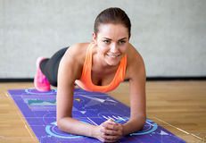 Le kvinnan som gör övningar på mattt i idrottshall Fotografering för Bildbyråer