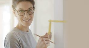 Le kvinnan som gör en hem- makeover och mäter med en linjal royaltyfri foto
