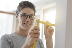Le kvinnan som gör en hem- makeover och mäter med en linjal royaltyfria bilder