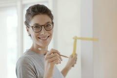 Le kvinnan som gör en hem- makeover och mäter med en linjal arkivfoton