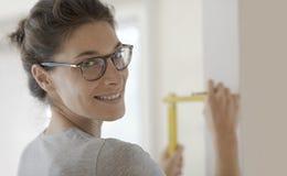 Le kvinnan som gör en hem- makeover och mäter med en linjal fotografering för bildbyråer