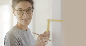 Le kvinnan som gör en hem- makeover och mäter med en linjal royaltyfri bild