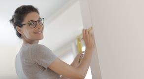 Le kvinnan som gör en hem- makeover och mäter med en linjal royaltyfri fotografi