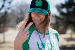Le kvinnan som ger fredtecknet på dagberöm för St Patricks royaltyfria foton