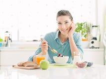 Le kvinnan som har frukosten hemma royaltyfria foton