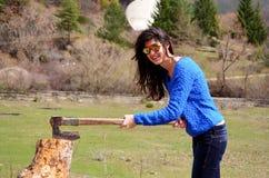 Le kvinnan som hugger av och blixtrande trä Arkivfoto