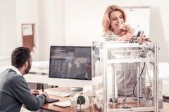 Le kvinnan som justerar skrivaren 3D på kontoret royaltyfria bilder