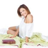 Le kvinnan som kopplar av på en säng royaltyfria foton