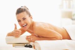 Le kvinnan som lägger på massage, bordlägga och visar upp tummar arkivfoton