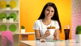 Le kvinnan som rymmer den disponibla bunken med frasig stekt kyckling som tycker om m?l fotografering för bildbyråer