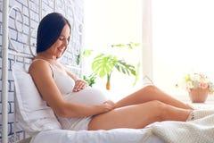 Le kvinnan som ser den gravida buken, når att ha väckt arkivfoton