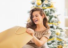 Le kvinnan som ser in i shoppingpåse nära julträd Arkivfoto
