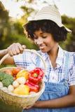 Le kvinnan som ser korgen av grönsaker Arkivbild