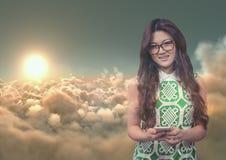 Le kvinnan som smsar mot molnig himmel med solbakgrund royaltyfri foto