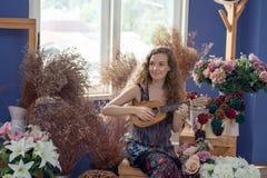 Le kvinnan som tycker om och kopplar av, genom att spela ukulelet i muen Royaltyfri Bild