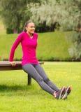 Le kvinnan som utomhus gör push-UPS på bänk Royaltyfria Bilder