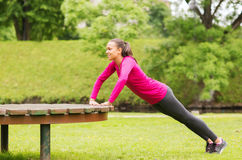 Le kvinnan som utomhus gör push-UPS på bänk Arkivbilder
