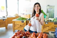 Le kvinnan som väljer stora tomater på, shoppa royaltyfria bilder