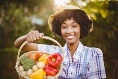 Le kvinnan som visar en korg av grönsaker Royaltyfria Bilder