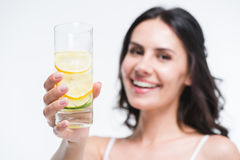 Le kvinnan som visar exponeringsglas av vatten med citronen Royaltyfri Foto