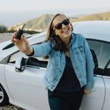 Le kvinnan som visar nya tangenter för uthyrnings- bil Arkivfoton