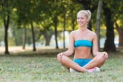Le kvinnan under yoga övar i parkera arkivfoto
