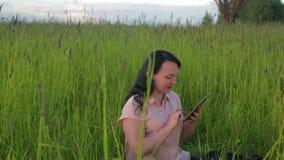 Le kvinnasammanträde i grönt gräs och arbete på minnestavlan parkera in bland planet Kameraflyttningarna till dockan arkivfilmer