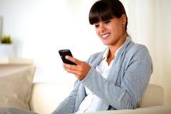 Le kvinnasammanträde på sofaen genom att använda henne mobiltelefon Arkivfoton