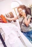 Le kvinnashopping i boutique och prata på telefonen arkivbild
