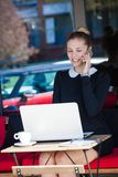 Le kvinnastudenten eller affär sitt i smar utomhus- bruk för kafét Arkivfoto