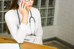 Le kvinnlig doktor Relaxing på hennes kontor, medan kalla till någon som använder en mobiltelefonnärbild Royaltyfria Foton