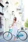 Le kvinnligt anseende bredvid en blå cykel på en härlig stadsgata Royaltyfri Bild