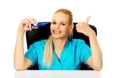 Le kvinnligt doktors- eller sjuksköterskasammanträde bak den hållande termometern och visningen för skrivbord tumma upp Royaltyfri Bild
