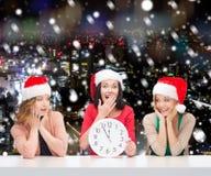 Le kvinnor i santa hjälpredahattar med klockan Arkivfoto