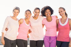Le kvinnor som bär rosa färger för bröstcancer Arkivbilder